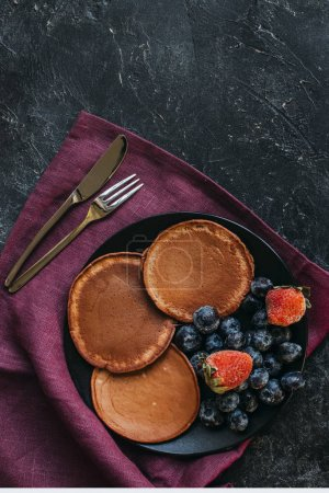 top view of chocolate pancakes with berries and cutlery on black concrete surface