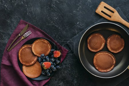 top view of fresh pancakes on plate and frying pan on black tabletop