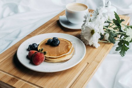 Photo for Breakfast in bed with pancakes and coffee on wooden tray - Royalty Free Image