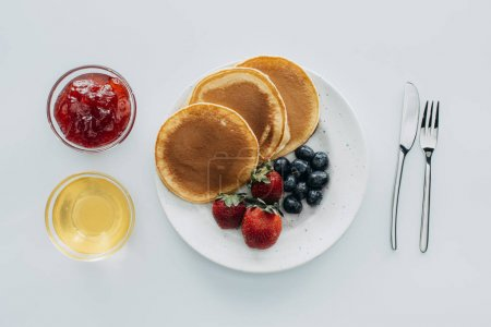 top view of sweet pancakes with berries on white table