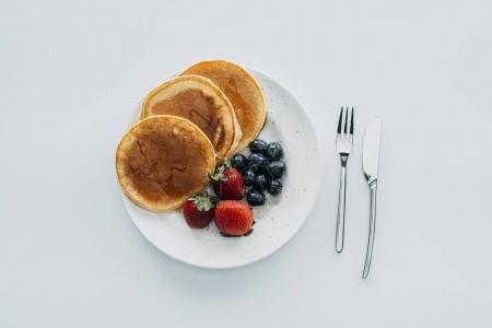 Photo for Top view of plate of pancakes with berries and cutlery on white table - Royalty Free Image