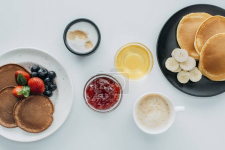 top view of breakfast for two with pancakes and coffee on white table