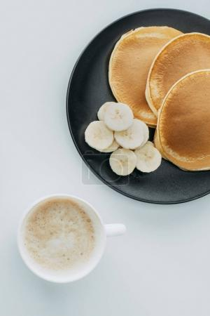 top view of pancakes with sliced banana and cup of coffee on white table