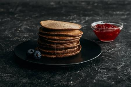 stacked chocolate pancakes with blueberries and bowl of jam