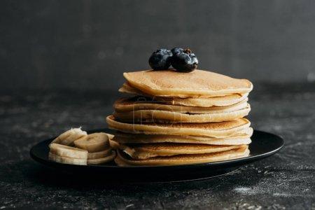 Foto de Deliciosos panqueques apilados con arándanos y plátano en rodajas - Imagen libre de derechos