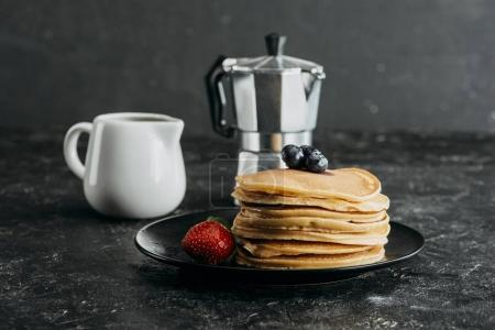 stack of freshly baked pancakes with mocha pot and milk jug