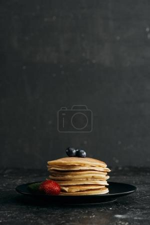 plate of delicious pancakes with berries on black concrete surface