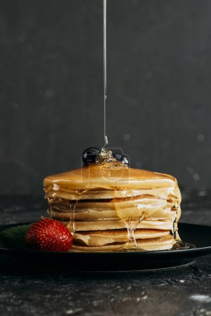 close-up shot of maple syrup pouring onto stacked pancakes