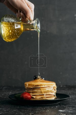cropped shot of woman pouring maple syrup onto stack of freshly baked pancakes