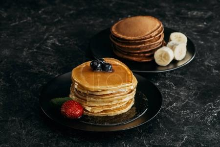 plates with stacks of tasty pancakes with fruits on black table