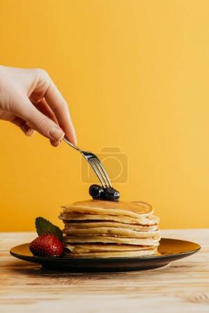 Photo for Cropped shot of woman taking pancakes from stack with fork - Royalty Free Image