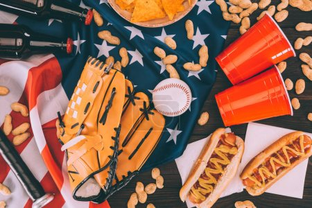 Photo pour Vue de dessus des hot dogs, gobelets en plastique, arachides, bouteilles de bière, balle de baseball et gant avec batte sur le drapeau américain - image libre de droit