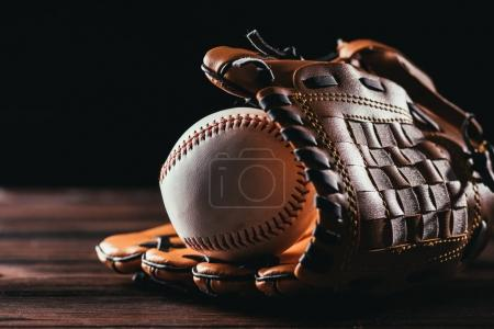 close-up view of white leather baseball ball and glove on wooden table