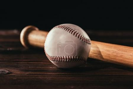 close-up view of white leather baseball ball and bat on wooden table