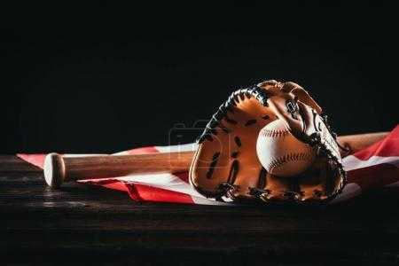 close-up view of baseball glove with ball and bat on wooden table and us flag on black