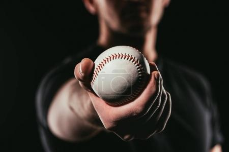 selective focus of man holding baseball ball isolated on black