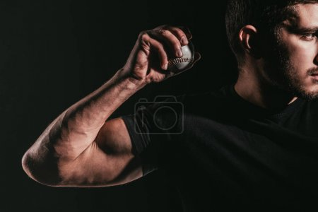 cropped shot of young muscular sportsman holding baseball ball isolated on black