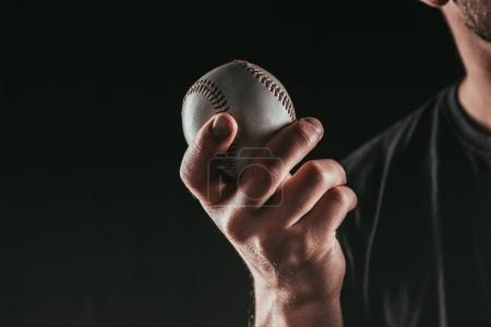 cropped shot of young sportsman holding baseball ball isolated on black