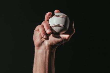 partial view of sportsman holding baseball ball isolated on black