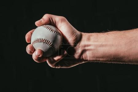 cropped shot of male hand holding baseball ball isolated on black