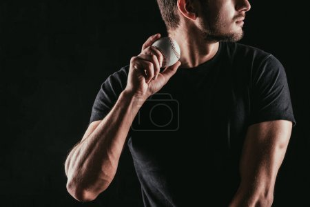 mid section of young man holding baseball ball isolated on black
