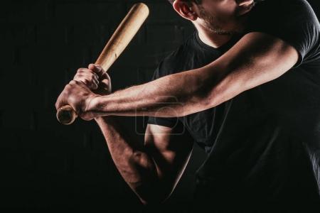 Photo pour Vue partielle du jeune sportif jouer au baseball avec batte isolée sur fond noir - image libre de droit