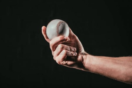 close-up partial view of male hand holding baseball ball isolated on black