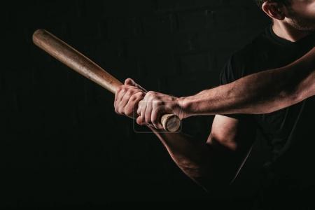 Photo pour Plan recadré de jeune homme jouant au baseball avec chauve-souris isolé sur noir - image libre de droit