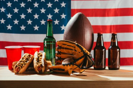 close-up view of beer with hot dogs and sport equipment with us flag behind