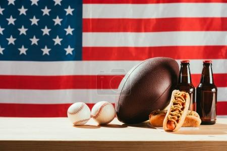 close-up view of hot dogs, beer bottles and balls on wooden table with us flag behind