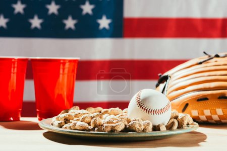 close-up view of baseball ball on plate with peanuts, red plastic cups and baseball glove on table with us flag behind