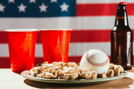 close-up view of baseball ball on plate with peanuts, red plastic cups and beer bottle on table