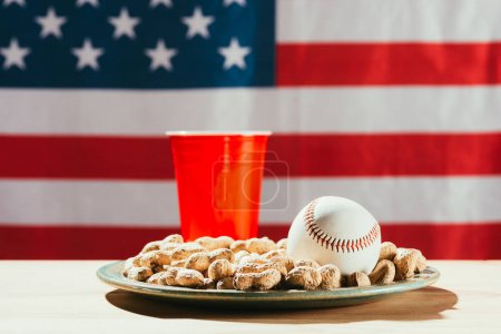 close-up view of baseball ball on plate with peanuts, red plastic bottle and american flag behind