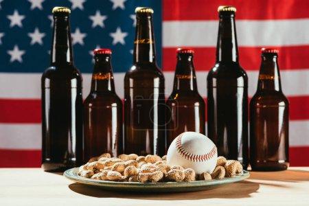 Photo pour Vue rapprochée de la balle de baseball sur la plaque avec les arachides et les bouteilles de bière avec un drapeau américain derrière - image libre de droit