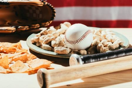 close-up view of baseball bats, baseball ball on plate with peanuts, snacks and leather glove on wooden table with us flag behind