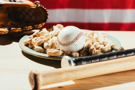 close-up view of baseball bats, baseball ball on plate with peanuts and leather glove on wooden table with us flag behind
