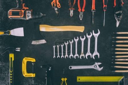 Foto de Lay Flat con hacha y varios dispuestos equipos de carpintería en superficie oscura - Imagen libre de derechos