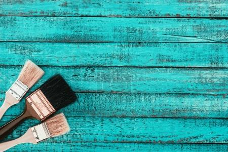 top view of arranged paint brushes for redecoration on blue wooden surface