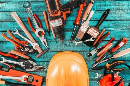 Photo pour Lay plat avec divers équipements de menuiserie avec casque au milieu sur une surface en bois bleue - image libre de droit