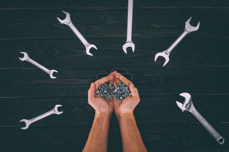 Photo pour Recadrée tir de mâles mains tenant des équipement de menuiserie avec clés autour sur table en bois - image libre de droit