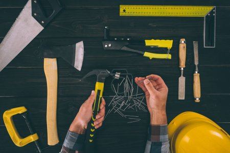 partial view of carpenter holding industrial tools in hands