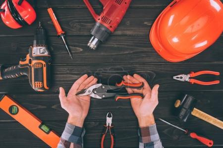 partial view of worker holding pliers with various supplies around on wooden surface