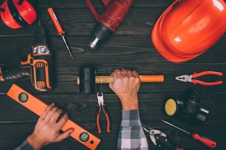 partial view of worker holding spirit level and hammer with various supplies around on wooden surface