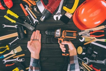 cropped shot of worker holding electric screwdriver and various supplies on wooden tabletop