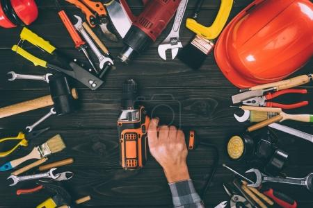 Photo for Cropped shot of worker holding electric screwdriver and various supplies on wooden tabletop - Royalty Free Image
