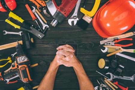 Photo for Partial view of hands in lock and carpentry equipment around on wooden surface - Royalty Free Image