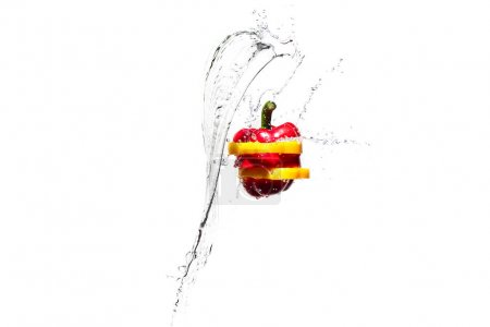 red and yellow bell pepper slices in water splashes isolated on white