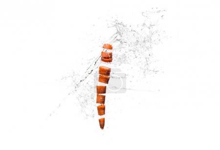 Fresh sliced carrot in water splashes isolated on white