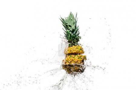 fresh sliced pineapple in water splashes isolated on white