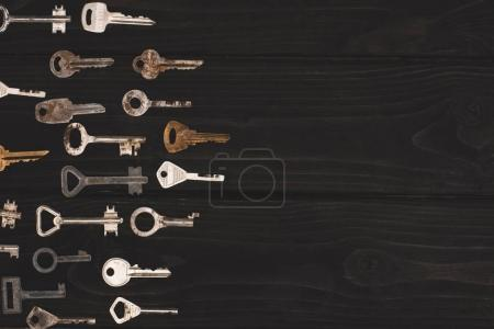 Photo for Top view of different vintage keys on black table - Royalty Free Image